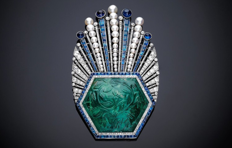 Ornament, Aigrette, Paul Iribe, Turban ornament with carved emerald of platinum, with a large hexagonal carved Indian emerald from 1850–1900, with millegrain-set diamonds and channel-set calibrécut sapphires.