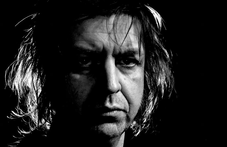 A dramatically backlit photograph of Piotr Uklanski in black-and-white