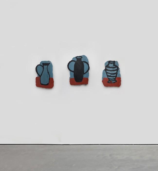 Trois vases archeologiques sur table rouge