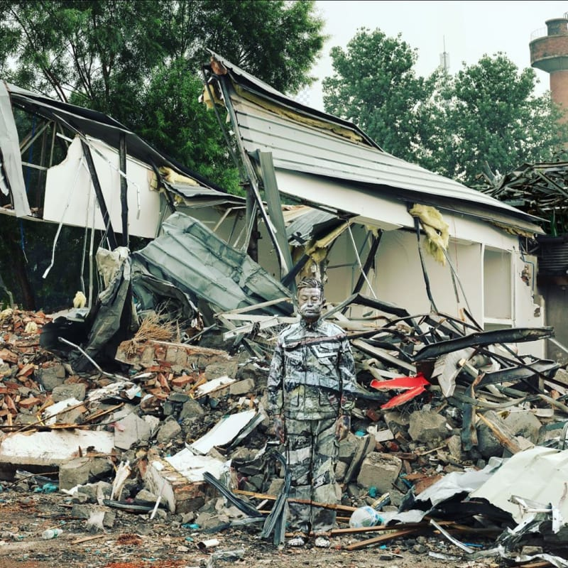 Liu Bolin frente a su taller en China destrudio nuevamente