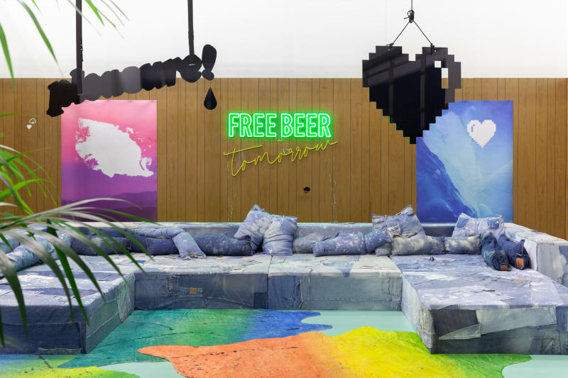 Wendy White. Free Beer Tomorrow, 2019. Hand- carved wood paneling, repurposed distressed denim, upholstery foam and wood custom furniture, digital prints on neoprene, hand painted faux calfskin rugs, paper cigarettes, custom floor paint, LED sign, live plants, Dimensions variable