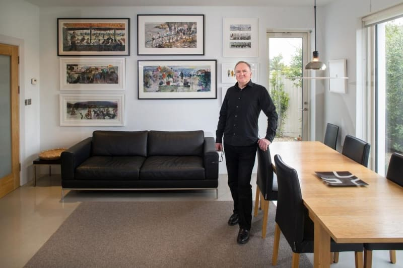 Artist John Short in the dining area of his newly remodelled house. Dating from the 1960s, the house now has higher ceilings, large expanses of glass and some concrete floors. The paintings will all feature in John's forthcoming exhibition