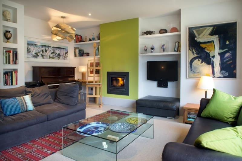 The living room is furnished with a mix of expensive and reasonably priced pieces, combining to create an edgy living space. John and Helen like colour, so they often change the lime panel to a different shade