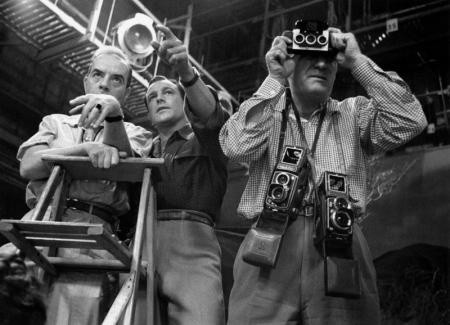 VINCENTE MINNELI AND GENE KELLEY DISCUSS THE PLACEMENT OF DANCERS ON 'BRIGADOON', WHILE MGM STILLS MAN ERIC CARPENTER TAKES A 3D PICTURE DOR THE DIRECTORS, MGM STUDIOS, 1954