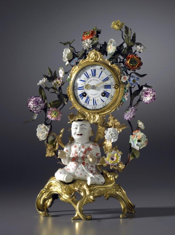A Louis XV gilt bronze and porcelain 'Pendule au Magot' , by Etienne Roquelon, The magot: China K'ang Hsi period (1662-1722). The gilt bronzes mounts: Paris, date circa 1745. The porcelain flowers: almost certainly Vincennes, date circa 1745