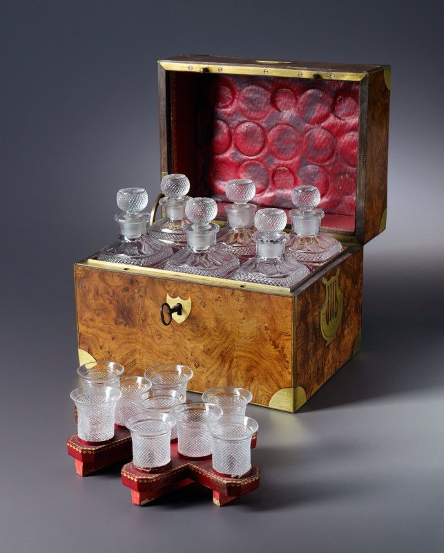 An Empire tantalus with six bottles and 9 glasses