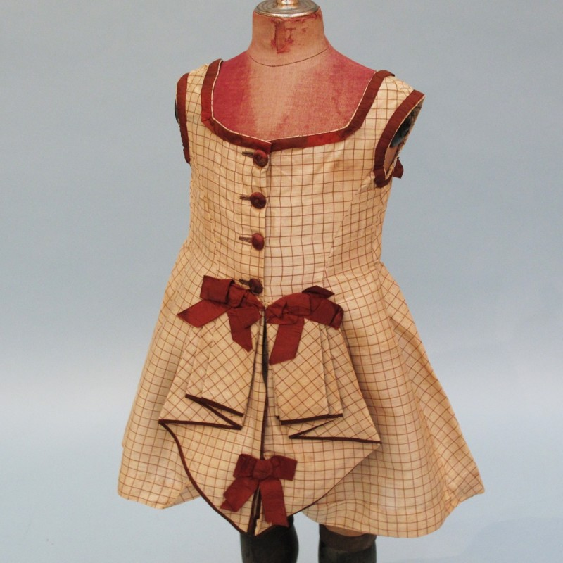 Victorian child's checked dress with brown ribbon trim.