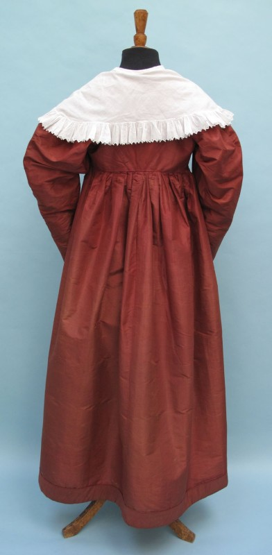 1830s wine coloured lady's silk dress with a pelerine of the period.