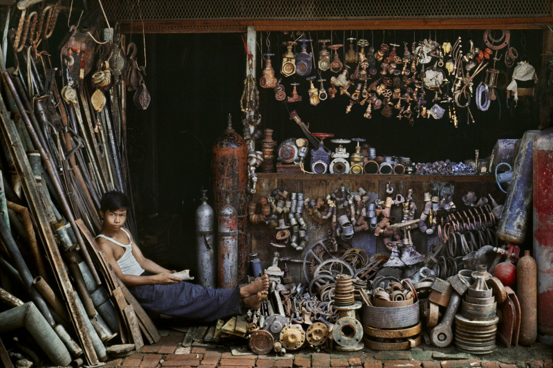 Steve McCurry, YOUNG SHOPKEEPER SELLING TOOLS, CAMBODIA