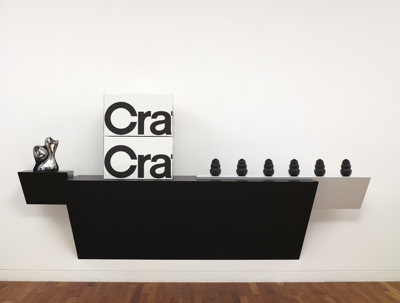 <p>Haim Steinbach, Crate & Barrel 2, 2008, plastic laminated wood shelf; 6 rubber dog chews; 2 'Crate & Barrel' cardboard boxes; stainless steel vase by Ron Arad, 59 x 117 1/4 x 26 in/ 150 x 297.8 x 66 cm</p>