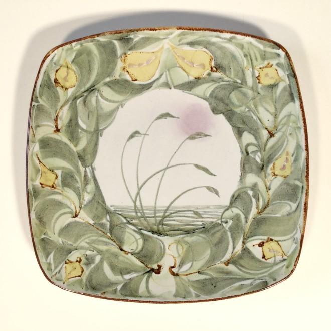 An Aldermaston Pottery square plate with a central reed design and a floral border
