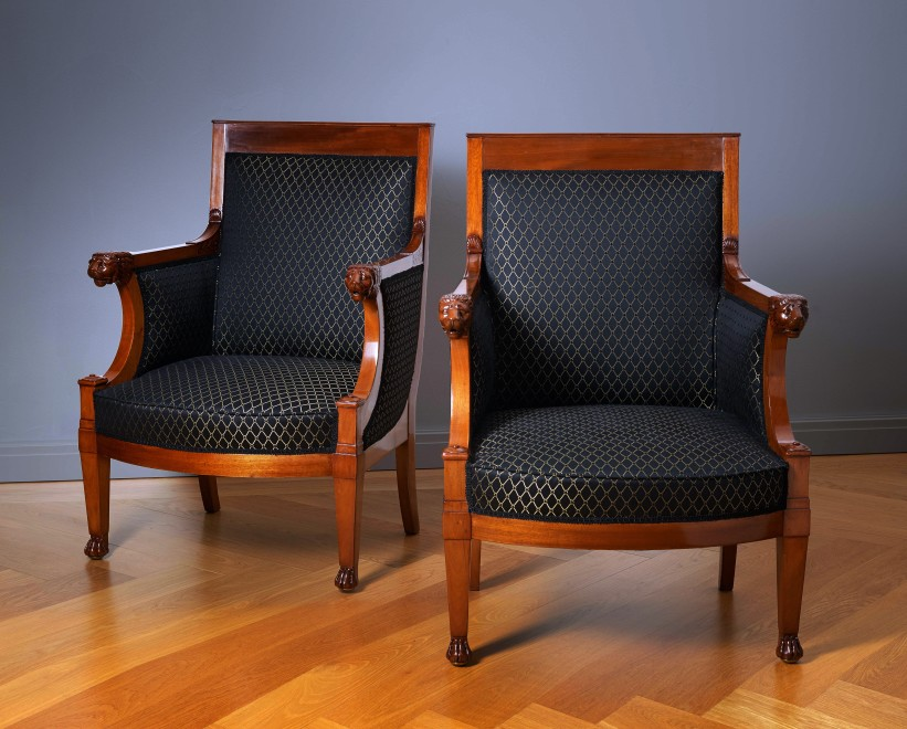 A pair of Empire fauteuils with arm rest terminating in carved lion heads, attributed to Jacob-Desmalter et Cie