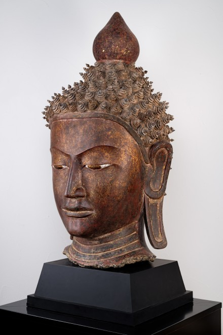 A nineteenth century Burmese carved and lacquered wooden head of Shakyamuni Buddha