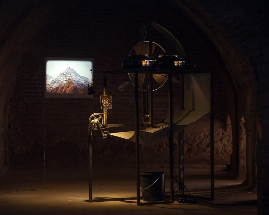 The Blue of the Distance, 2012 Steel, bike components, 2 x 35mm slides and projectors, tarpaulin, ice, bucket. Installation view Marrakech Bienniale 2012 190 x 120 x 300 cm 74 3/4 x 47 1/4 x 118 1/8 in (variable)