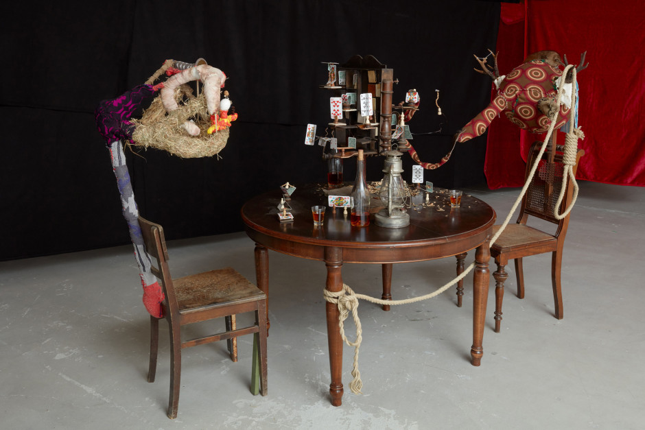 Skat Chess, 2017  wooden chairs, wooden table, wood, chess piece, whiskey, bottle, glasses, play dough, socks, deer antlers, stuffed muskrat, straw, egg shells, fabric, buttons  151 x 222 x 119 cm  59 ½ x 87 ⅜ x 46 ⅞ in.