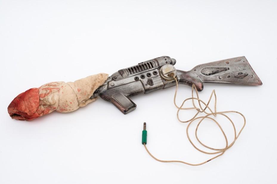 <p>Jeff Keen,&#160;<em>Silverhead's Gun</em>, 1960s, spraypaint, cloth, plastic gun, string, wire, 9 x 68 x 13 cm, 3 1/2 x 26 3/4 x 5 1/8 in</p>